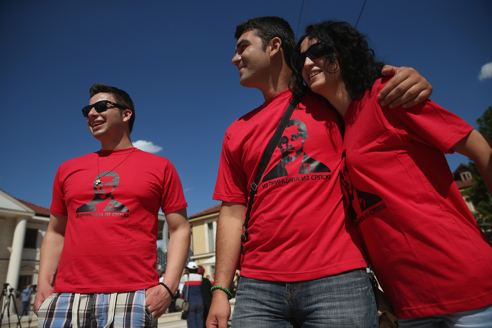 . Visitors wearing t-shirts that depict Serbian secessionist Gavrilo Princip, the assassin of Austrian Archduke Franz Ferdinand and his wife, Duchess Sophie, walk trhough the mock-village of Andricgrad on St. Vitus Day in Srpska Republika on June 28, 2014 in Visegrad, Bosnia and Herzegovina. Serbian leaders are scheduled to hold ceremonies at Andricgrad later in the day to mark the centenary of the assassination of the Archduke on June 28, 1914, an event that propelled Europe into World War I. The city of Sarajevo is holding its own commemoration, though Serbian leaders are boycotting the Sarajevo events, claiming the Bosniaks have turned the commemoration too partisan. Andricgrad was built by Serbian film director Emir Kusturica and will become the set for a film about Yugoslav poet Ivo Andric.  (Photo by Sean Gallup/Getty Images)