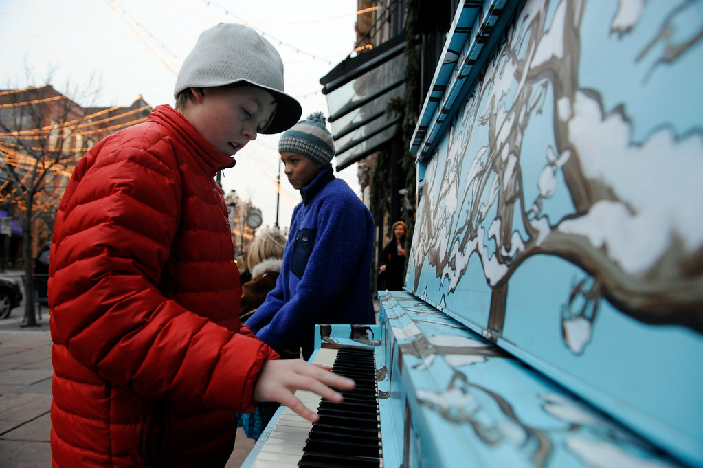 """. Ian Hastings, 13-years-old, left, plays an upright piano at the corner of 15th and Larimer St. in downtown Denver Tuesday evening. Hasting\'s friend, Sam Von Mettenheim, 12-years-old, right, listens. The two just, along with family and friends just came from the play, A Christmas Carol from the Denver Center for the Performing Arts. The piano is part of a program called \""""Your Keys to the City,\"""" part of an interactive public art installation is part of the \""""Winter in the City\"""" holiday initiative,  launched by the Downtown Denver Partnership and the Downtown Denver Business Improvement District. Their are five painted pianos placed around downtown that the public can play at their leisure.   (Andy Cross, The Denver Post)"""