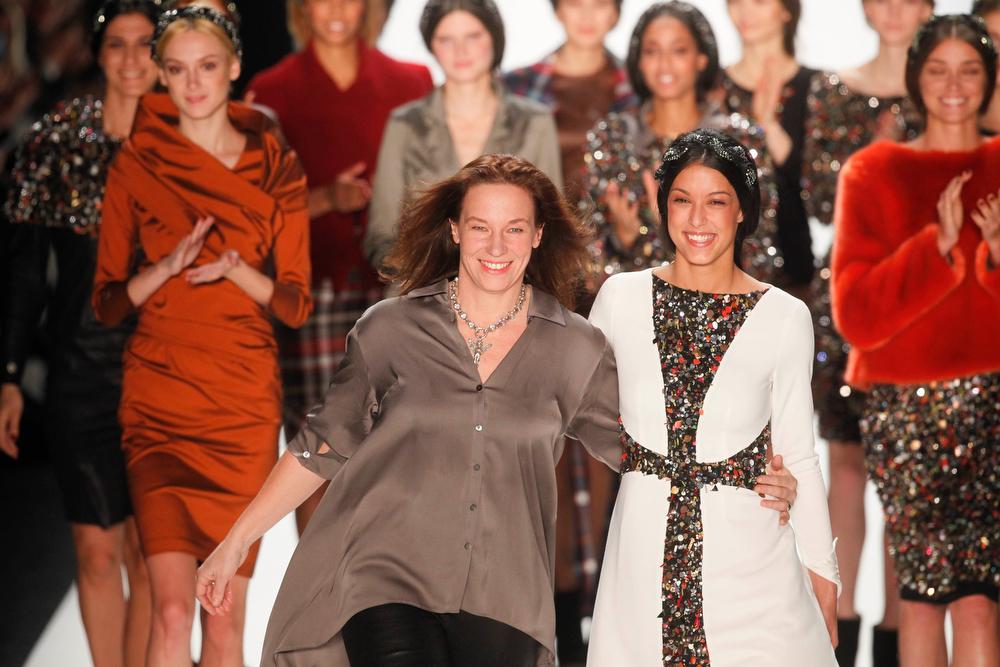 . Designer Anja Gockel, left. receives applause after the presentation of her Autumn Winter 2014 collection during the Mercedes Benz Fashion Week in Berlin, Wednesday, Jan. 15, 2014. (AP Photo/Markus Schreiber)