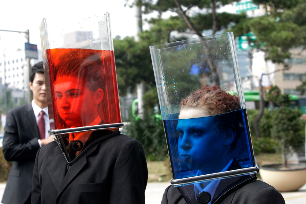 ". Australian Matina Moutzouris, left, and Samantha Hickey, members of street performance group Erth, wearing transparent boxes with water walk around the street during their street performance ""Waterheads\"" in Seoul, South Korea, Wednesday, Oct. 6, 2010. The performance is part of the Hi Seoul Festival. (AP Photo/Ahn Young-joon)"