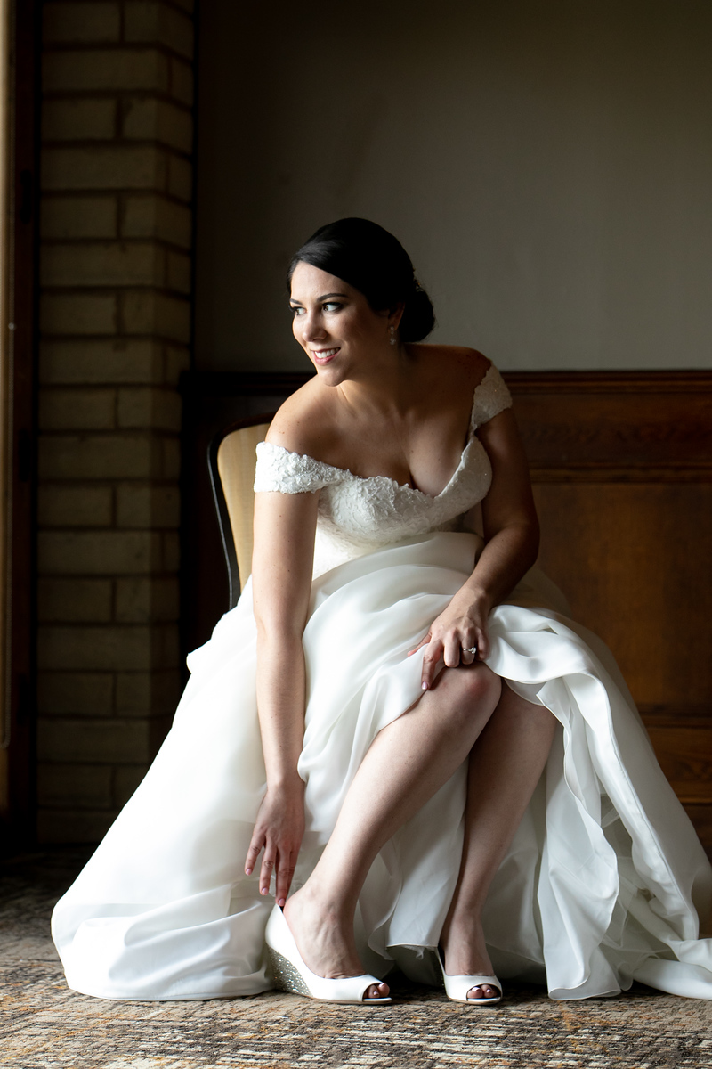 bride slipping on her shoes while smiling towards and open window