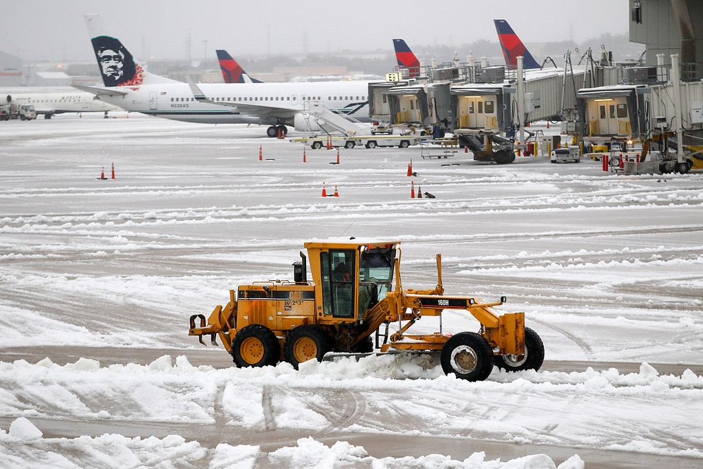 . Snow removal equipment clears the wet sleet on the ramp area at Dallas-Fort Worth International Airport, Friday, Dec. 6, 2013.  The weather forced more than 1,000 cancellations at Dallas-Fort Worth International Airport, one of the nation\'s busiest airports and a key hub for Fort Worth-based American Airlines. Many travelers were stuck waiting and hoping for another flight to take them to their destination.  (AP Photo/The Dallas Morning News, Tom Fox)