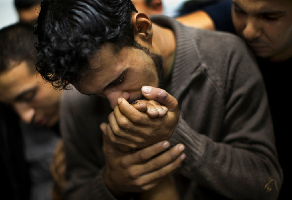 . In this Nov. 18, 2012 file photo, a Palestinian man kisses the hand of a dead relative in the morgue of Shifa Hospital in Gaza City. This photo was one in a series of images by Associated Press photographer Bernat Armangue that won the first place prize in the World Press Photo 2013 photo contest for the Spot News series category.  (AP Photo/Bernat Armangue, File)