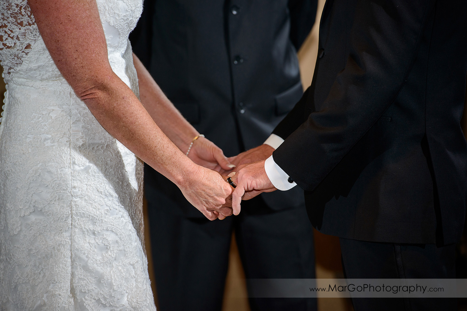 bride and groom holding hands at wedding ceremony at Clubhouse at Las Positas Golf Course in Livermore