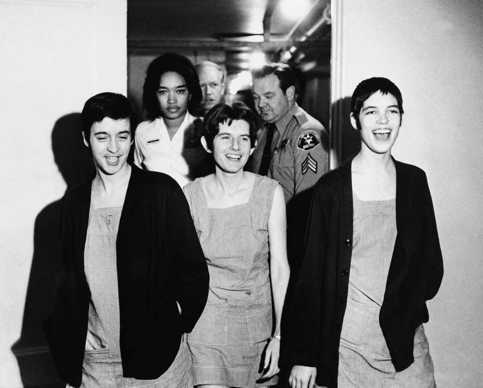 . Three women co-defendants in the Sharon Tate murder case, from left, Susan Atkins, Patricia Krenwinkel and Leslie Van Houten, laugh as they walk to court in Los Angeles for sentencing, March 29, 1971.  They angrily shouted at the judge when they were in the courtroom and were ejected, along with Charles Manson, before the jury sentenced them to death in the gas chamber. (AP Photo)