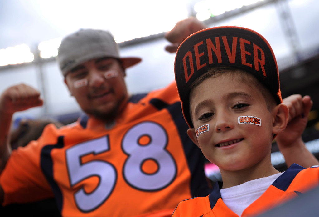 . DENVER, CO. - AUGUST 03: Elijah Martinez got front row seats with his father Steve Saturday night for practice. Denver Broncos fans waited inside Sports Authority Field Saturday night, August 3, 2013 hoping the weather would clear so that the team could practice.  Photo By Karl Gehring/The Denver Post