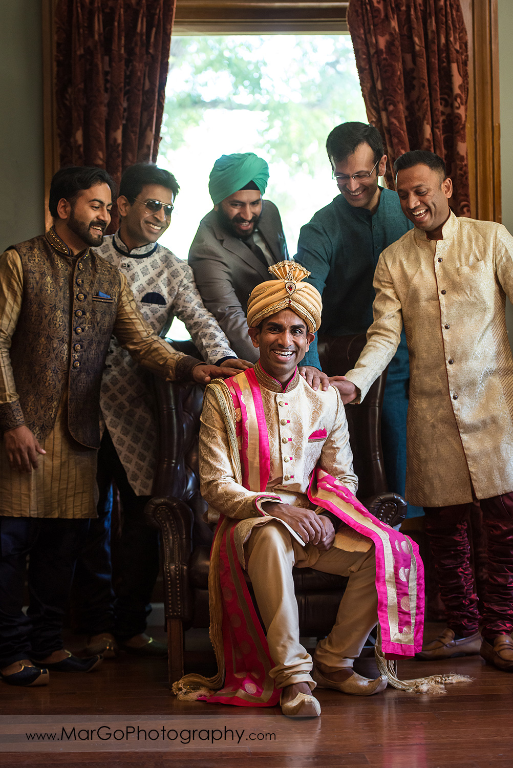 Indian groom sitting on leather chair with groomsmen at Elliston Vineyards in Sunol