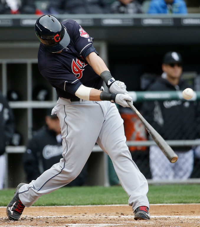 . Cleveland Indians\' Yan Gomes hits a sacrifice fly against the Chicago White Sox during the first inning of a baseball game Friday, April 8, 2016, in Chicago. (AP Photo/Nam Y. Huh)