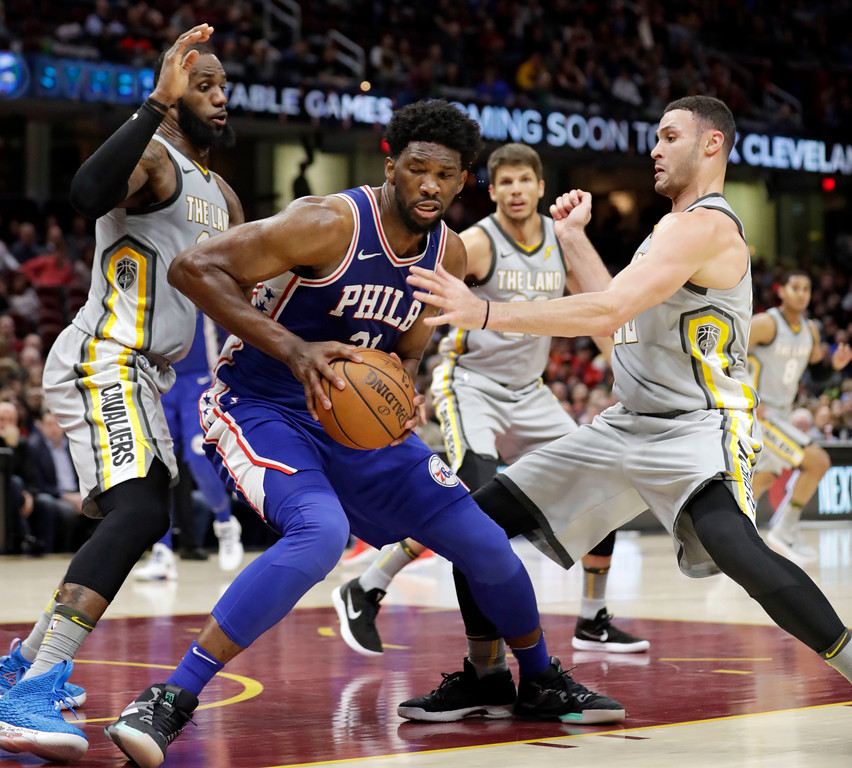 . Philadelphia 76ers\' Joel Embiid, center, from Cameroon, dribbles against Cleveland Cavaliers\' LeBron James and Larry Nance Jr. in the second half of an NBA basketball game, Thursday, March 1, 2018, in Cleveland. (AP Photo/Tony Dejak)