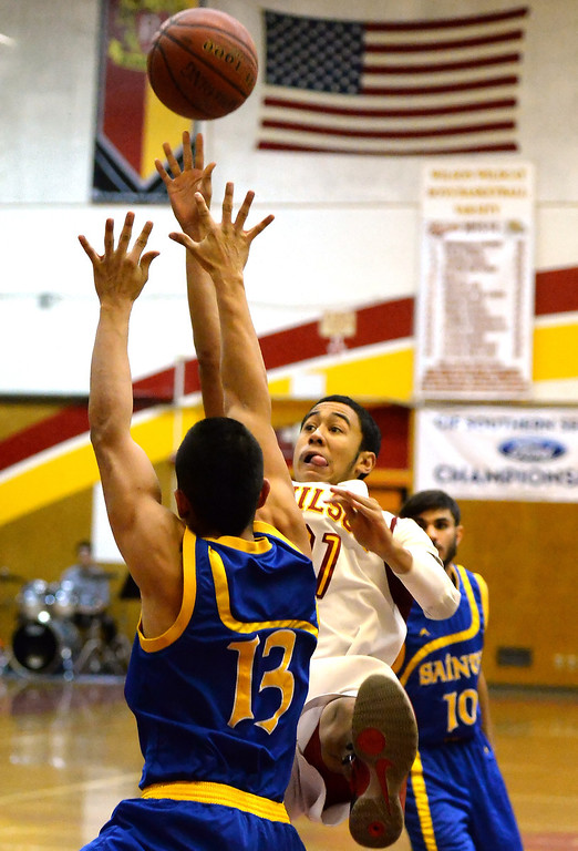 . Wilson\'s Kevin Price (21) shoots over San Dimas\' Tony Hugo (13) as Travis Schiewe (C) (10) looks on in the first half of a prep basketball game at Wilson High School in Hacienda Heights, Calif., on Friday, Jan. 31, 2014. (Keith Birmingham Pasadena Star-News)