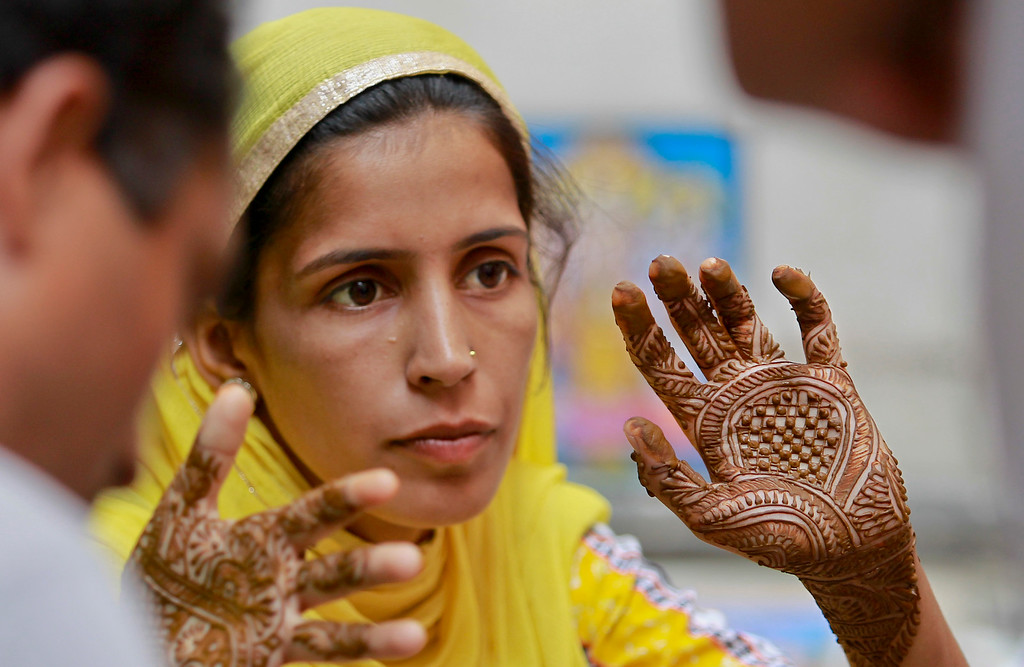 . An Indian Muslim woman gets henna designs applied on their hand on the eve of Eid al Adha, in Jammu, India, Monday, Sept.12, 2016. Muslims around the world celebrate Eid al-Adha, or the Feast of the Sacrifice, by sacrificing animals to commemorate Prophet Ibrahim\'s faith in being willing to sacrifice his son. (AP Photo/Channi Anand)