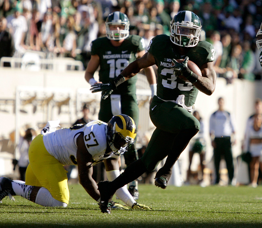 . Michigan State\'s Jeremy Langford (33) rushes past Michigan\'s Frank Clark (57) as Michigan State quarterback Connor Cook (18) watches during the first quarter of an NCAA college football game, Saturday, Oct. 25, 2014, in East Lansing, Mich. (AP Photo/Al Goldis)