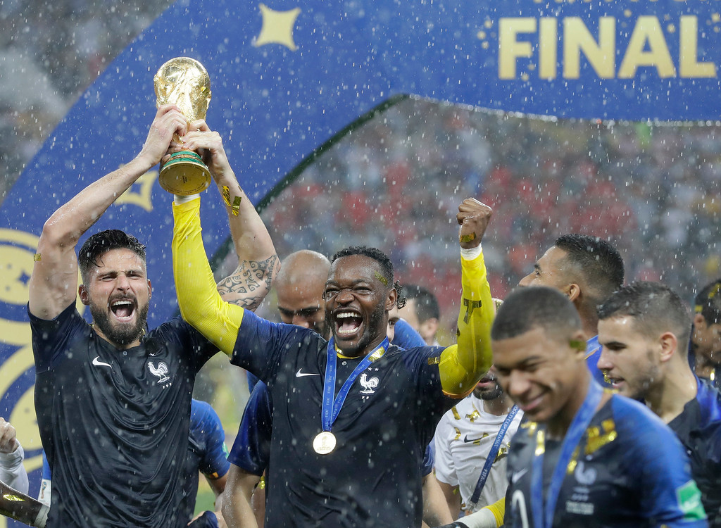 . France\'s Olivier Giroud, left, celebrates with the trophy after the final match between France and Croatia at the 2018 soccer World Cup in the Luzhniki Stadium in Moscow, Russia, Sunday, July 15, 2018. France won the final 4-2. (AP Photo/Matthias Schrader)
