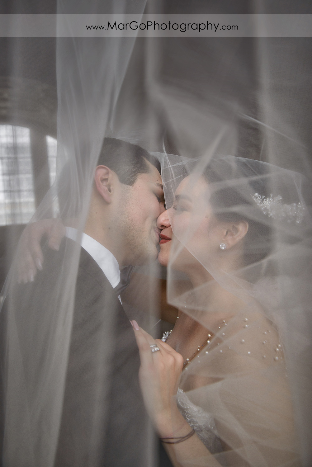 bride and groom under the veil in San Francisco City Hall