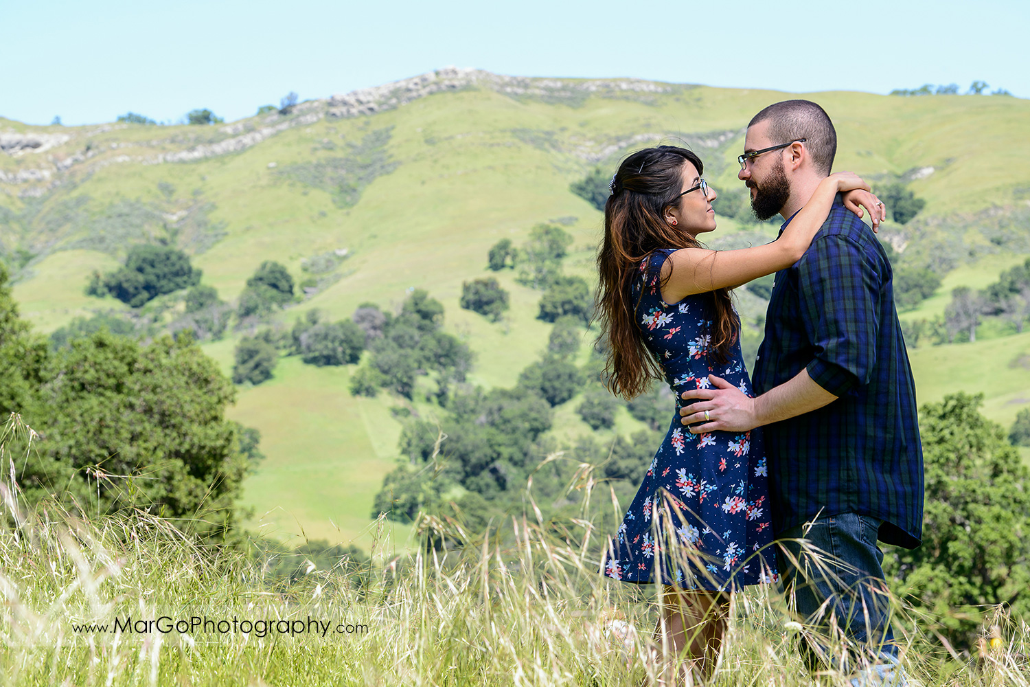 3/4 portrait of woman in blue dress and man in blue shirt facing each other during engagement session at Sunol Regional Wilderness