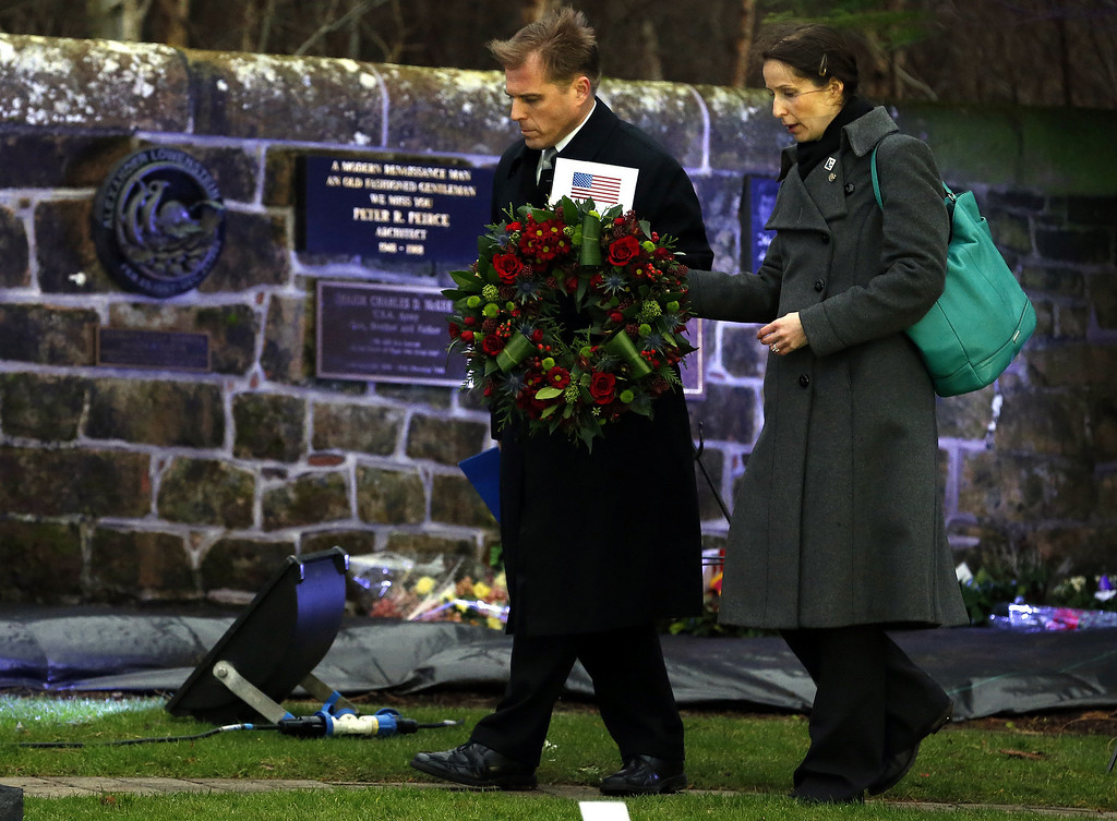 . Craig Lynes, left, US government representative and Zoja Bazarnic, right, U.S consulate principal officer carry a wreath to the main memorial stone in memory of the victims of the Lockerbie Pan Am flight 103 bombing in the garden of remembrance at Dryfesdale Cemetery, near Lockerbie, Scotland. Saturday Dec. 21, 2013. (AP Photo/Scott Heppell).