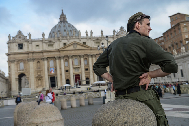 . A tourist stays in front of the Basilica in Saint Peter\'s Square on April 26, 2014 in Vatican City, Vatican. The late Popes John Paul II and John XXIII will be canonised on April 27 inside the Vatican with 800,000 pilgrims from around the world expected to attend.  (Photo by Giorgio Cosulich/Getty Images)