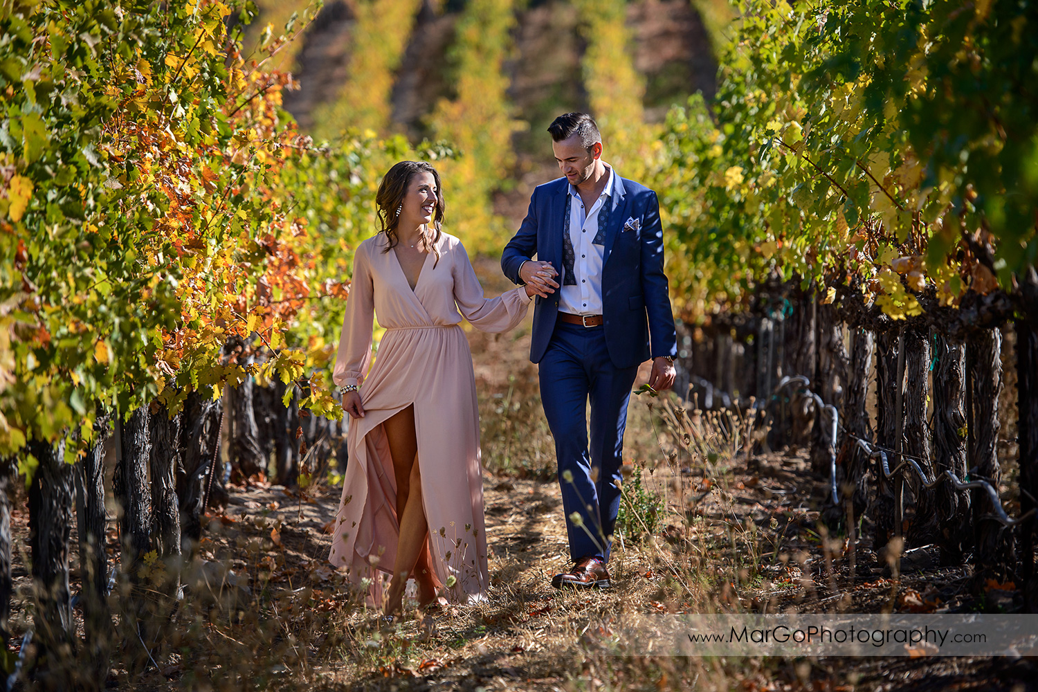 woman in pink dress and man in blue suit holding hands and walking in vineyard during Napa Valley engagement session at Castello di Amorosa in Calistoga