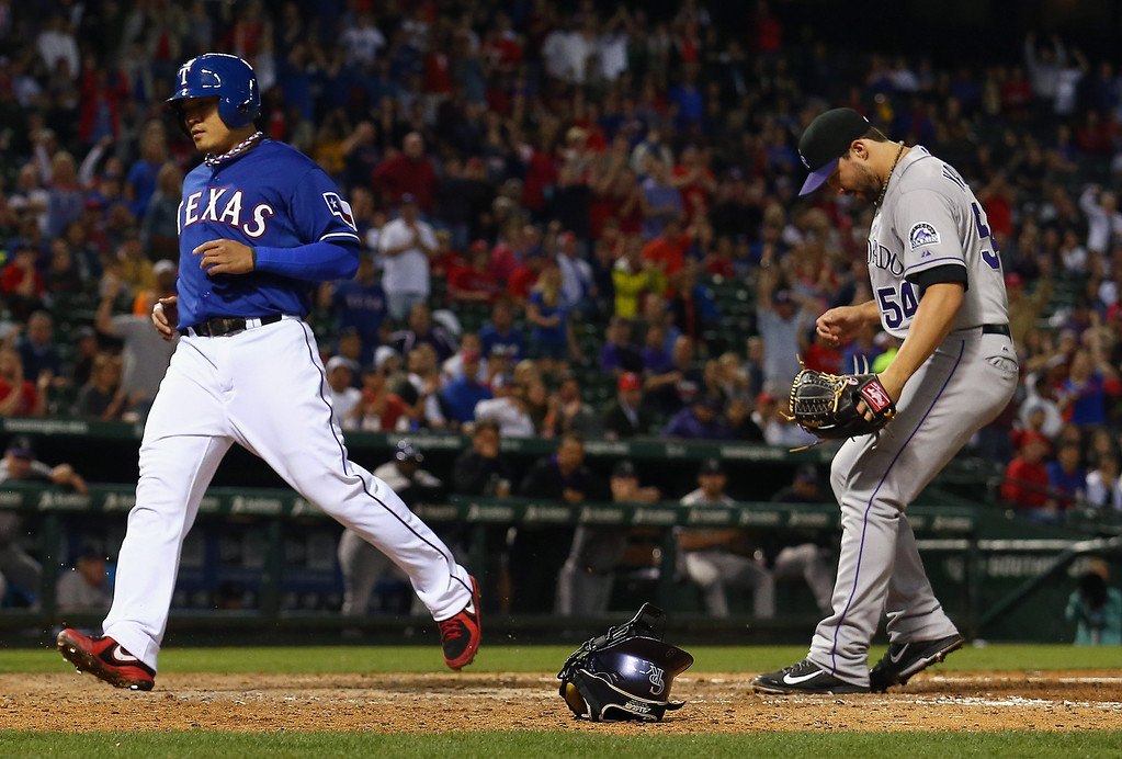 . ARLINGTON, TX - MAY 08:  Shin-Soo Choo #17 of the Texas Rangers scores on a wild pitch thrown by Tommy Kahnle #54 of the Colorado Rockies in the bottom of the seventh inning at Globe Life Park in Arlington on May 8, 2014 in Arlington, Texas.  (Photo by Tom Pennington/Getty Images)