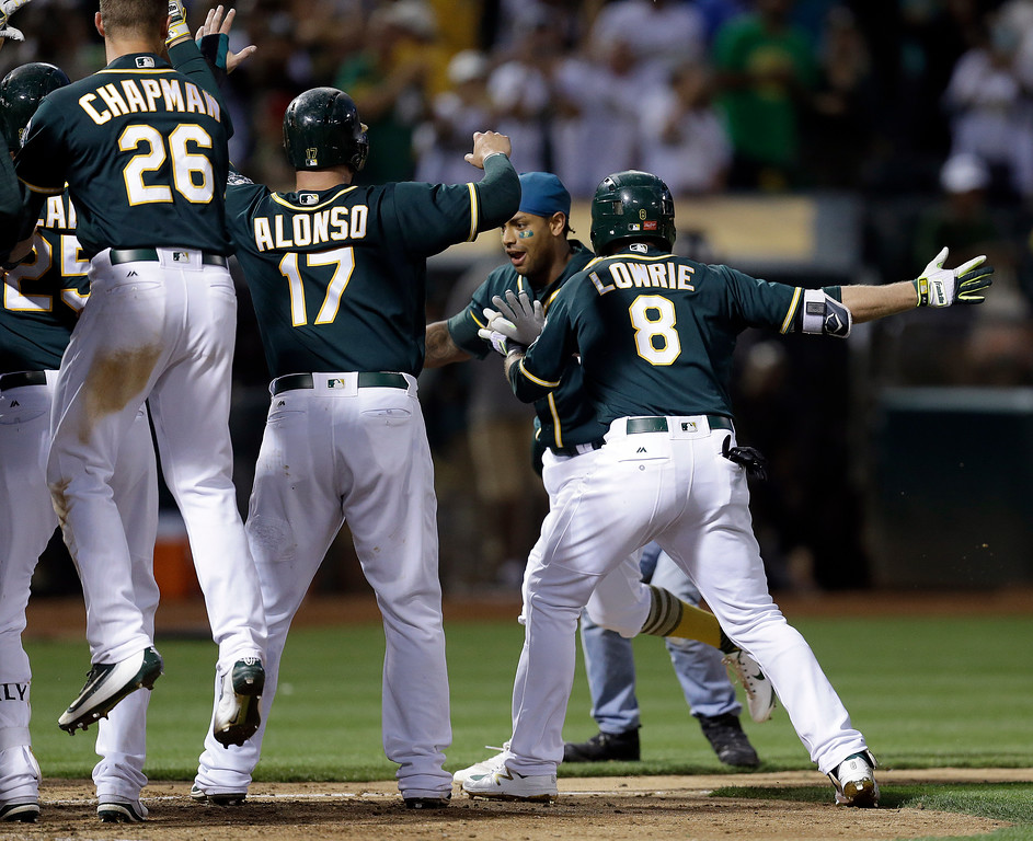 . Oakland Athletics\' Khris Davis, second from right, is mobbed by teammates, including Matt Chapman (26), Yonder Alonso (17) and Jed Lowrie (8), after hitting a two-run home run off Cleveland Indians\' Bryan Shaw during the ninth inning of a baseball game Saturday, July 15, 2017, in Oakland, Calif. The A\'s won 5-3. (AP Photo/Ben Margot)