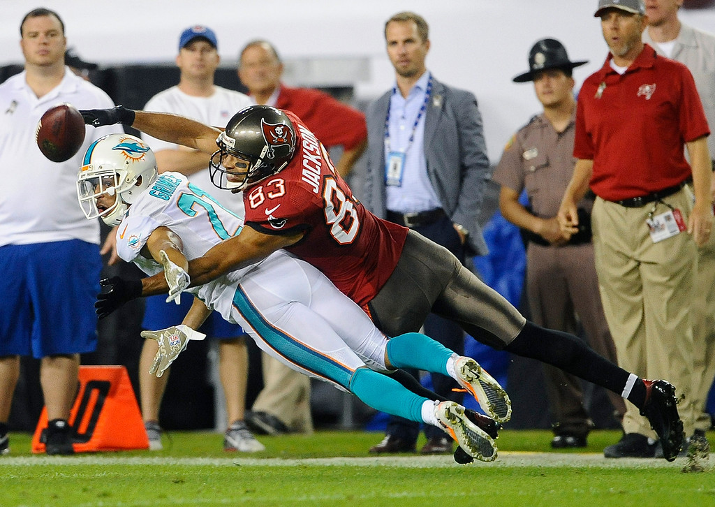 . Tampa Bay Buccaneers wide receiver Vincent Jackson (83) reaches for a pass over Miami Dolphins cornerback Brent Grimes (21) during the first quarter of an NFL football game Monday, Nov. 11, 2013, in Tampa, Fla. (AP Photo/Brian Blanco)