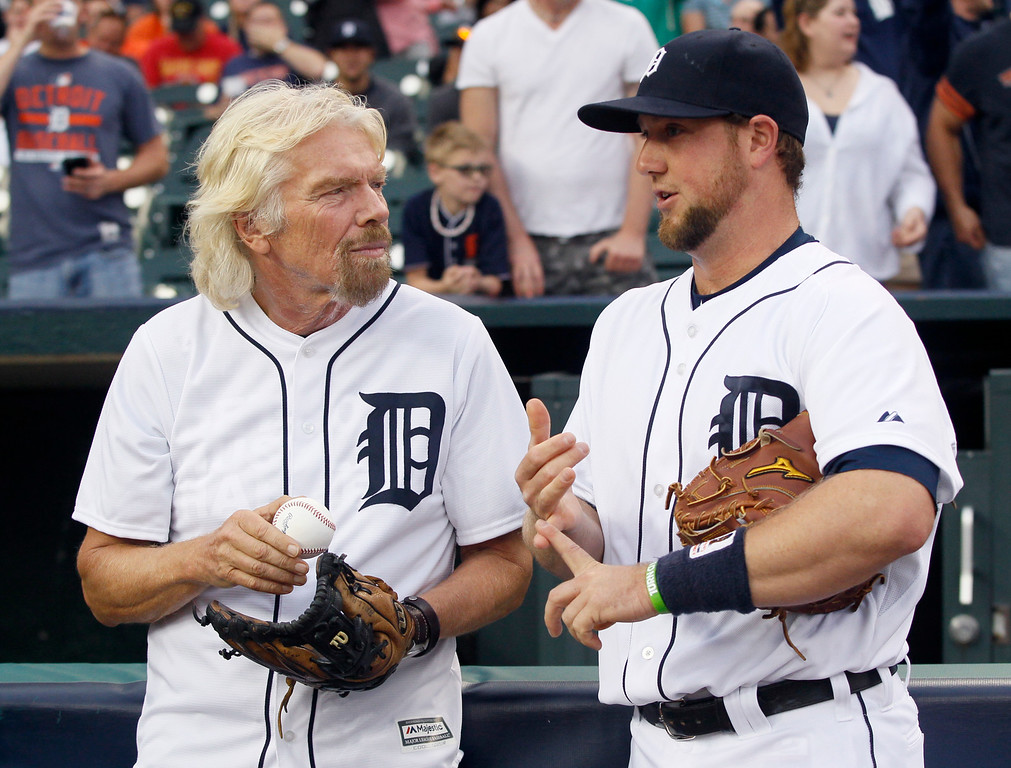 . Sir Richard Branson, president and founder of Virgin Atlantic, talks with Detroit Tigers catcher Bryan Holaday before throwing out a ceremonial first pitch for their baseball game against the Cleveland Indians at Comerica Park Friday, June 12, 2015, in Detroit. Branson was in town to kick off Virgin Atlantic Airlines new route from Detroit to London. (AP Photo/Duane Burleson)