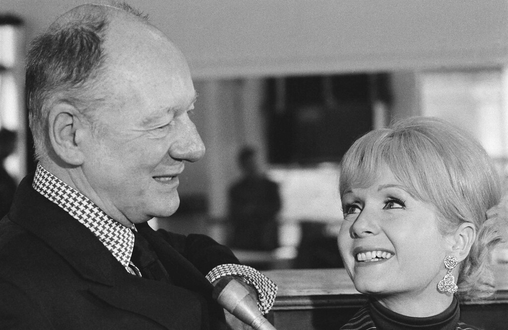 ". Film actress Debbie Reynolds, who will make her first Broadway appearance in the title role of the musical ""Irene,\"" looks up to director Sir John Gielgud during an interview at New York rehearsal hall, Oct. 23, 1972. The show opened on Broadway in January. (AP Photo/Marty Lederhandler)"