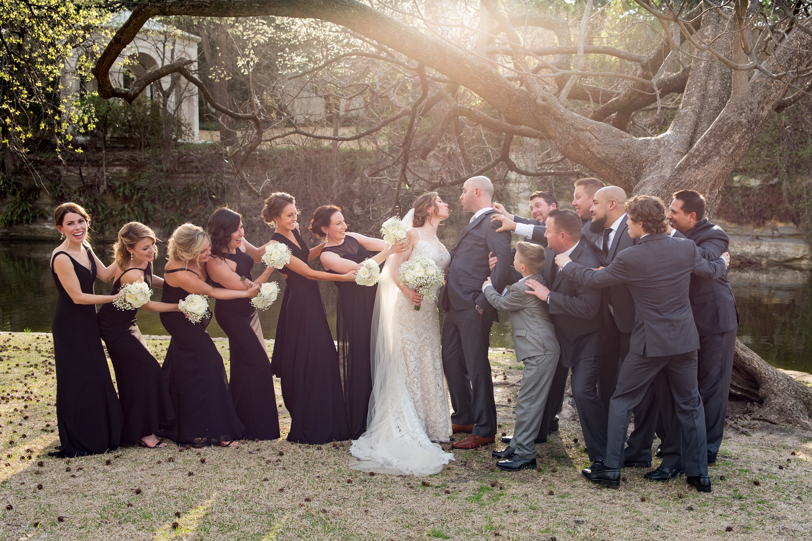 a bride and groom humorously being pulled apart by their wedding party of 6 bridesmaids and 6 groomsmen