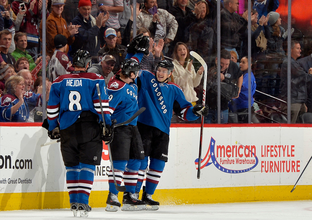 . Colorado Avalanche center Nathan MacKinnon, center, is congratulated by teammates John Mitchell (7) and Jan Hejda (8) after scoring a goal against the Minnesota Wild during the second period of an NHL hockey game on Saturday, Nov. 30, 2013, in Denver. (AP Photo/Jack Dempsey)