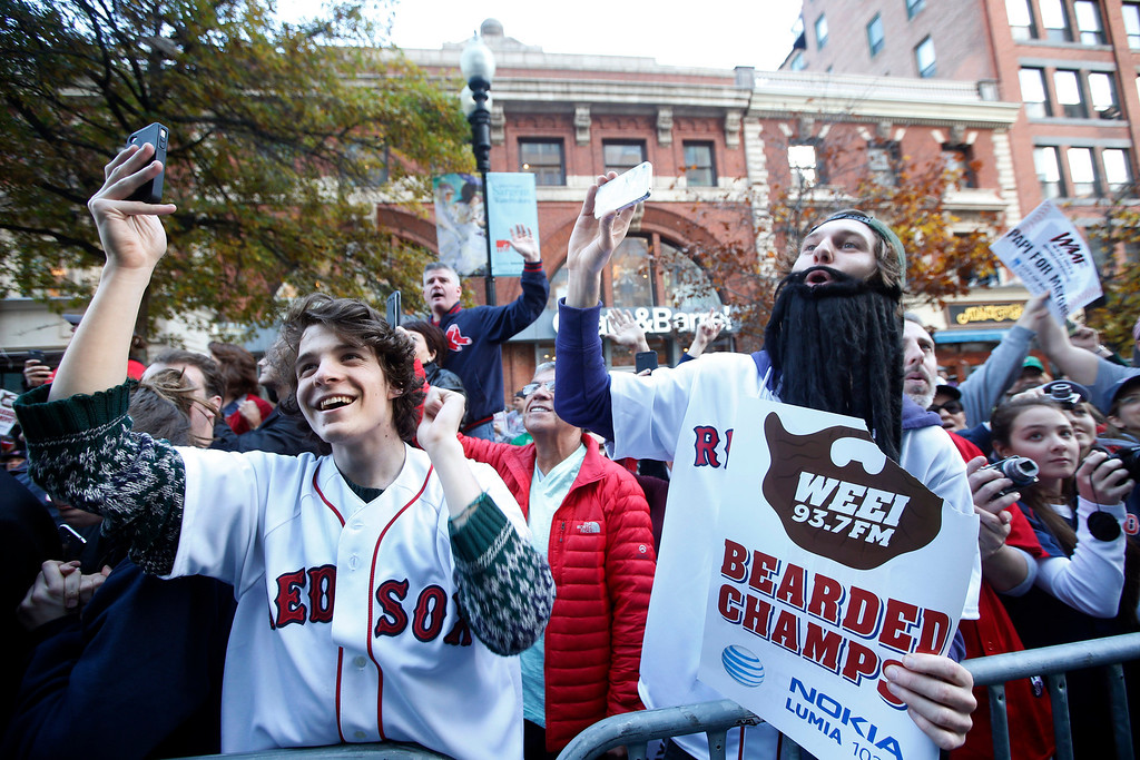 . Boston Red Sox fans cheer as they watch a rolling rally of duck boats pass by during a celebration of the team\'s World Series baseball championship in Boston, Saturday, Nov. 2, 2013. (AP Photo/Elise Amendola)