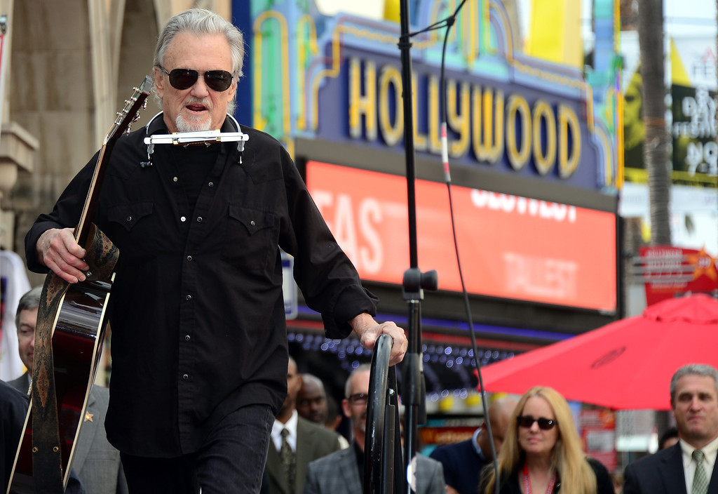 """. Kris Kristofferson arrives on stage to perform \""""Me & Bobby McGee\"""" live on Hollywood Boulevard during posthumous Star ceremony for the late Janis Joplin on November 4, 2013 in Hollywood, California. Joplin, who had her siblings Michael and Laura at the ceremony, would have turned 70 years old this year and is the recipient of the 2,510th Star on the Hollywood Walk of Fame in the Category of Recording.         (FREDERIC J. BROWN/AFP/Getty Images)"""
