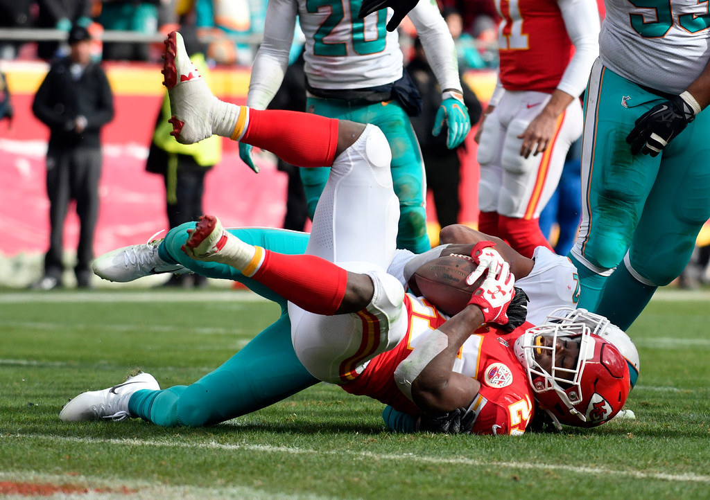 . Kansas City Chiefs running back Kareem Hunt (27) is tackled by Miami Dolphins safety T.J. McDonald, rear, during the first half of an NFL football game in Kansas City, Mo., Sunday, Dec. 24, 2017. (AP Photo/Ed Zurga)