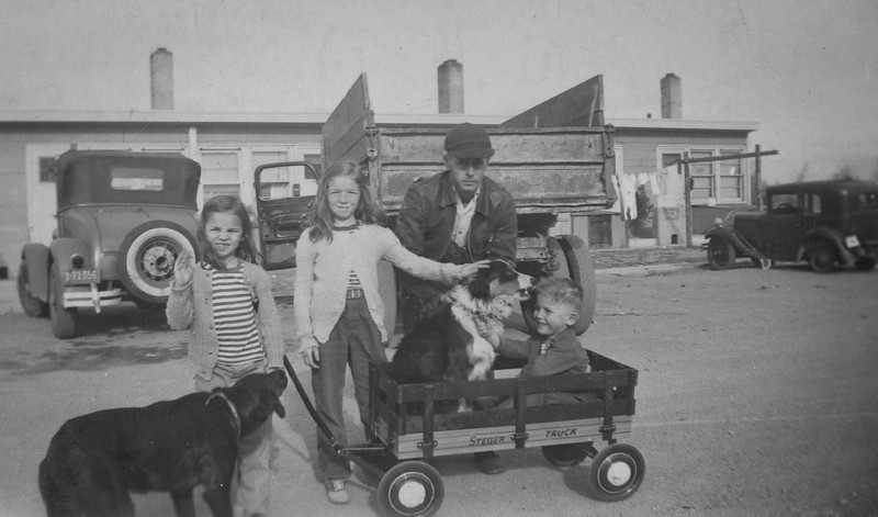 Cherry, Carol and Elmer Burgin with George in the wagon and their dog Shep and another dog. Cheyenne, Wyoming 1940's