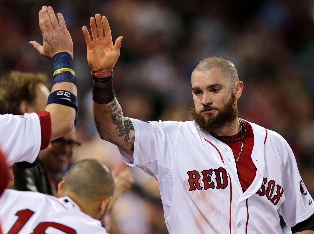 . Boston Red Sox\'s Jonny Gomes is congratulated after scoring in the fourth inning of Game 2 of baseball\'s American League division series against the Tampa Bay Rays, Saturday, Oct. 5, 2013, in Boston. (AP Photo/Charles Krupa)