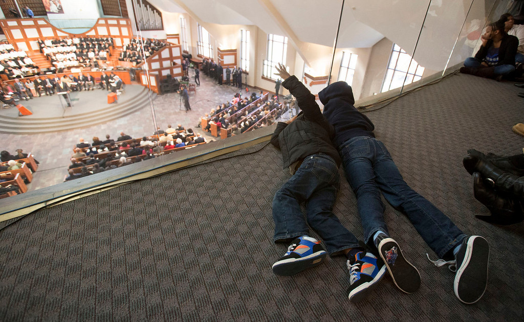 . Brothers Lotanna, 6, left, and Kelo Ekwegbalu, 6, of Powder Springs, Ga., lay on the ground of the balcony during the Rev. Martin Luther King Jr. holiday commemorative service at Ebenezer Baptist Church Monday, Jan. 20, 2014, in Atlanta. (AP Photo/Jason Getz)