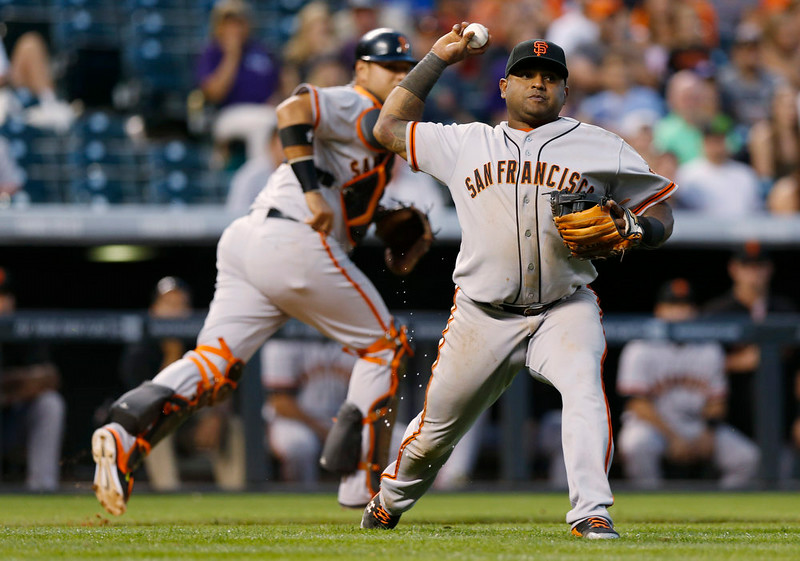 . San Francisco Giants third baseman Pablo Sandoval, front, throws to first base after fielding sacrifice bunt off the bat of Colorado Rockies\' Josh Rutledge in the ninth inning of the Rockies\' 10-9 victory in a baseball game in Denver on Monday, Sept. 1, 2014. Giants catcher Guillermo Quiroz, back, covers on the play. (AP Photo/David Zalubowski)
