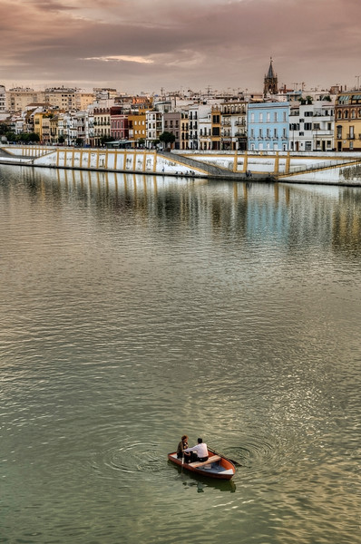 Couple rowing a boat along the Guadalquivir river with the Triana neighbourhood in the background. 