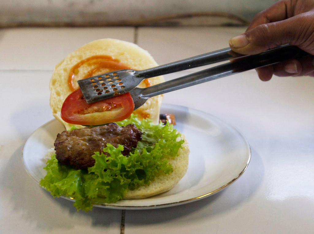 . A chef prepares a cobra meat burger at a Chinese restaurant in the ancient city of Yogyakarta April 1, 2011. Snake hunters catch about 1,000 cobras from Yogyakarta, Central Java and East Java provinces each week to harvest their meat for burgers, priced at 10,000 rupiah ($1.15) each, as well as satay and other dishes. Some customers said they believe cobra meat can cure skin diseases and asthma, and increase sexual virility. Picture taken April 1, 2011. REUTERS/Dwi Oblo