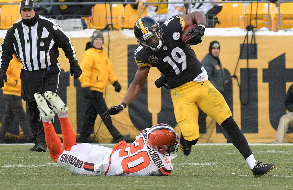 . Pittsburgh Steelers wide receiver JuJu Smith-Schuster (19) eludes the tackle by Cleveland Browns strong safety Briean Boddy-Calhoun (20) during the second half of an NFL football game in Pittsburgh, Sunday, Dec. 31, 2017. (AP Photo/Don Wright)