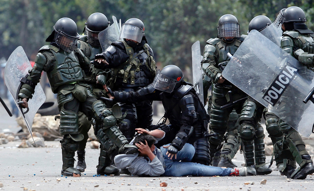 . A riot police officer, left, kicks a protester as another, center, tries to protect him before his arrest during protests in Ubate, north of Bogota, Colombia, Monday, Aug. 26, 2013.  Hundreds of protesters clashed with police in support of farmers who have being blockading Colombian highways for a week for an assortment of demands that include reduced gasoline prices, increased subsidies and the cancellation of free trade agreements. (AP Photo/Fernando Vergara)