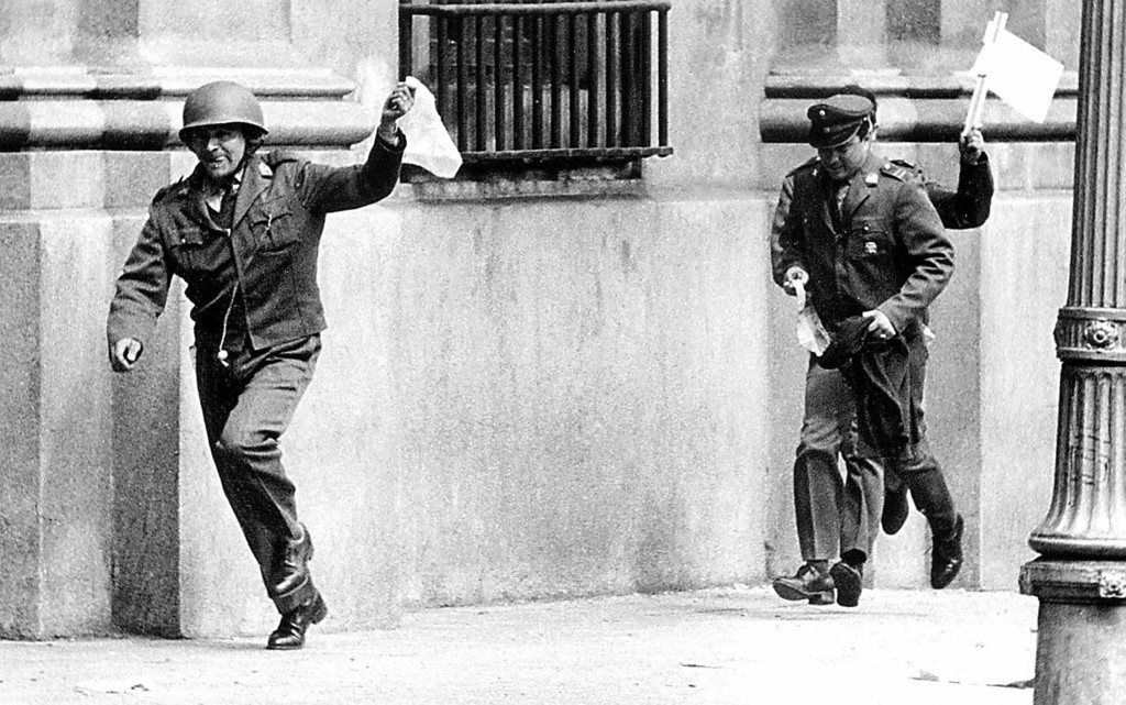 . In this Sept. 11, 1973 file photo, police officers assigned to guard the presidential palace La Moneda, in Santiago, Chile, hold out white flags as they surrender during the military coup led by Gen. Augusto Pinochet, overthrowing President Salvador Allende. The Sept. 11 coup initially was supported by many Chileans fed up with inflation that topped 500 percent, chronic shortages and factory takeovers. But it destroyed what they had proudly described as South America\'s strongest democracy. (AP Photo/Alberto Bravo, File)