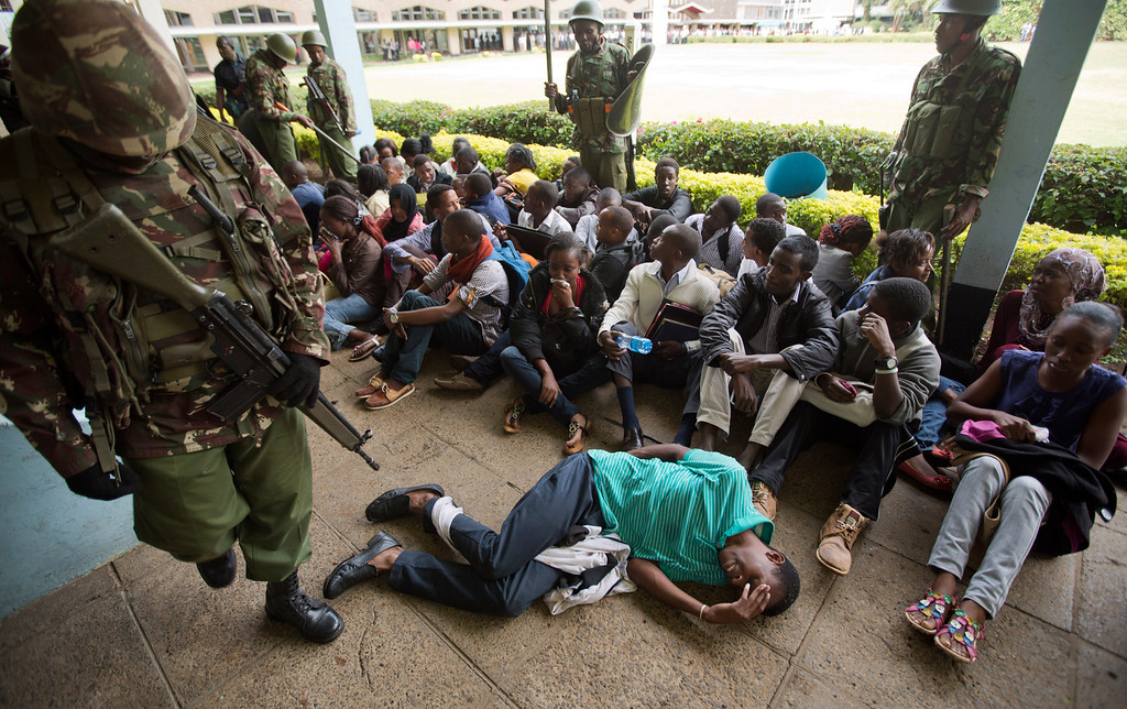 . A Kenyan student with an injured leg lies in front of a group of other detained students after they surrendered to riot police in order to escape from a tear-gas-filled building inside Nairobi University\'s main campus in downtown Nairobi, Kenya Tuesday, May 20, 2014. Kenyan university students on Tuesday carried out demonstrations over a proposed increase in student fees, but the protests quickly turned into hours of running battles between students throwing rocks and security forces firing tear gas, before riot police chased the students inside their campus and cornered them in a building into which they fired dozens of tear gas grenades and for a while prevented anyone from leaving. (AP Photo/Ben Curtis)