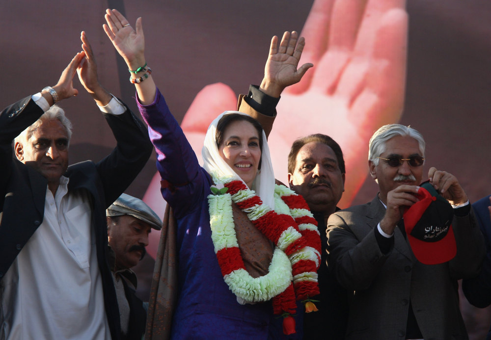Description of . RAWALPINDI, PAKISTAN - DECEMBER 27:  Former Prime Minister Benazir Bhutto (C) waves to supporters at a campaign rally December 27, 2007 in Rawalpindi, Pakistan. She was assassinated as she left the event, while waving to the crowd through the sun roof of her armored car.  (Photo by John Moore/Getty Images)