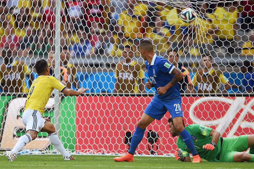 . Colombia\'s forward Teofilo Gutierrez (L) scores his team\'s second goal during a group C football match between Colombia and Greece at the Mineirao Arena in Belo Horizonte during the 2014 FIFA World Cup on June 14, 2014.   AFP PHOTO / PEDRO UGARTE