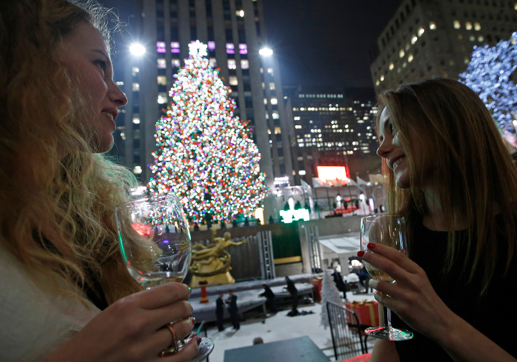 . Anna Ladner, left, and Vanja Ojes Dahlberg sip Champagne in front of the Rockefeller Center Christmas tree after it was lit, Wednesday, Dec. 4, 2013, in New York. Some 45,000 energy efficient LED lights adorn the 76-foot tree. (AP Photo/Kathy Willens)