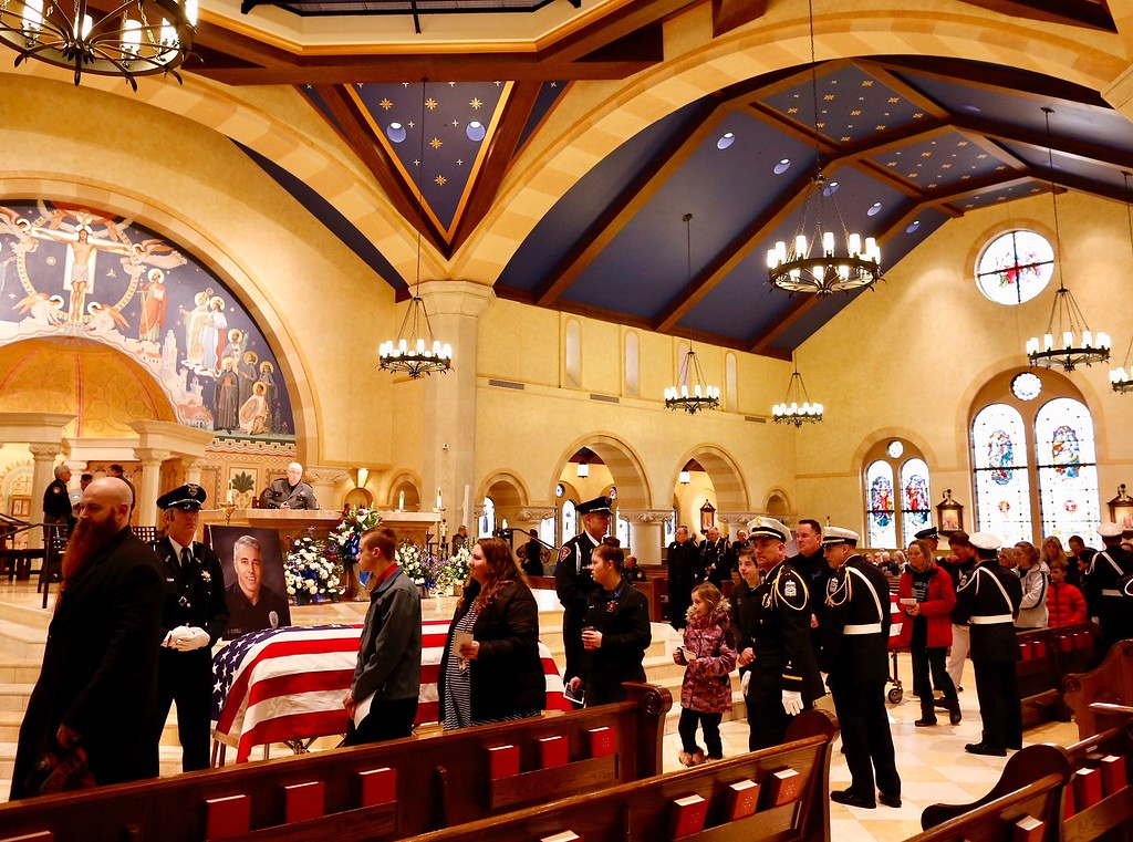 . Westerville residents view the caskets of Westerville Police officers Anthony Morelli and Eric Joering at St. Paul Catholic Church, Westerville, Ohio on Friday, Feb. 16, 2018.  The two veteran officers were shot after entering a residence Saturday. The officers returned fire, wounding 30-year-old Quentin Smith, who has been charged with aggravated murder and remains hospitalized.  (Kyle Robertson  /The Columbus Dispatch via AP, Pool)