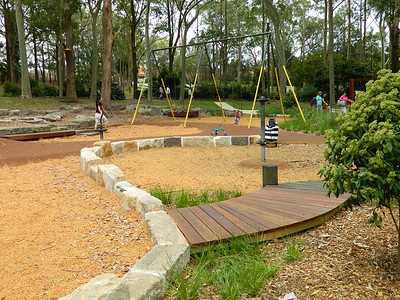 curved raised timber pathway with round posts and sandstone block retaining wall and spinners metal swing