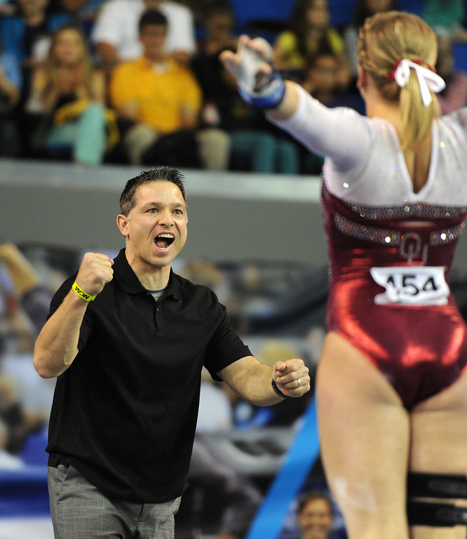 . Oklahoma assistant coach Lou Ball cheers as Rebecca Clark finishes on the uneven parallel bars at the NCAA Women\'s Gymnastics Championship Team Finals at Pauley Pavilion, Saturday, April 20, 2013. Oklahoma finished second in the competition. (Michael Owen Baker/Staff Photographer)
