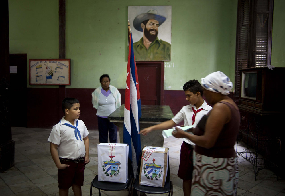 Description of . Under an image of Cuba's revolutionary hero Camilo Cienfuegos, Cuban schoolchildren help a voter to properly cast her ballot at a polling station during parliament elections in Havana, Cuba, Sunday, Feb. 3, 2013. More than 8 million islanders are eligible to vote and will approve 612 members of the National Assembly and over 1,600 provincial delegates. (AP Photo/Ramon Espinosa)