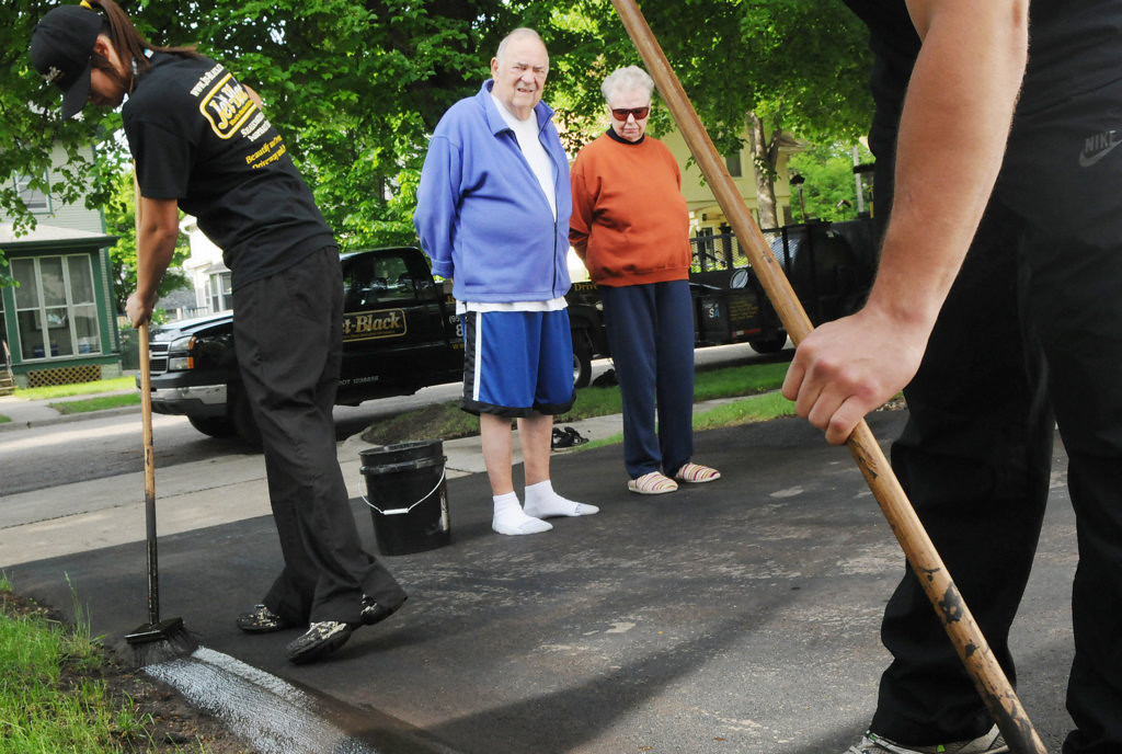 . Bob and Opal Kuehn watch a crew from Jet-Black reseal their driveway in St. Paul after scammers shoddily resealed it in mid-May.  (Pioneer Press: Jean Pieri)